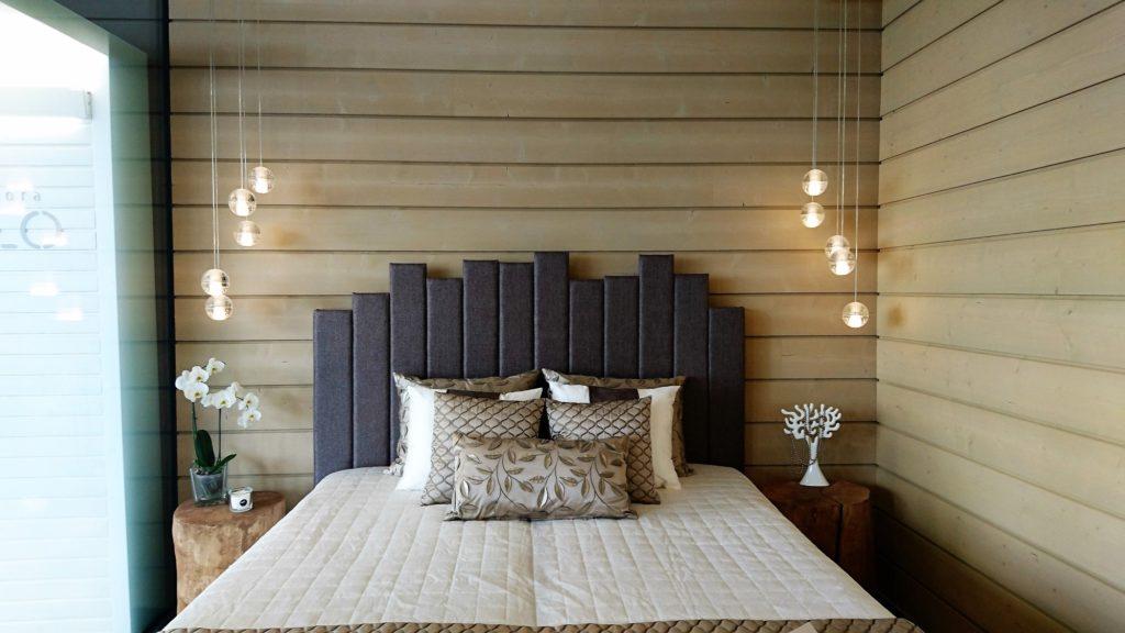 Sisustusinspiraatiota asuntomessuilta: Kevyet valaisimet, leikkisä sängynpääty sekä rouheat puupaneelit ovat toimiva yhdistelmä