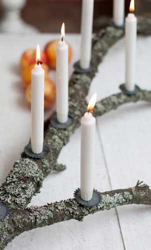 Jouluaatto: Oksalla palavat kynttilät ovat kauniin yksinkertaisia.